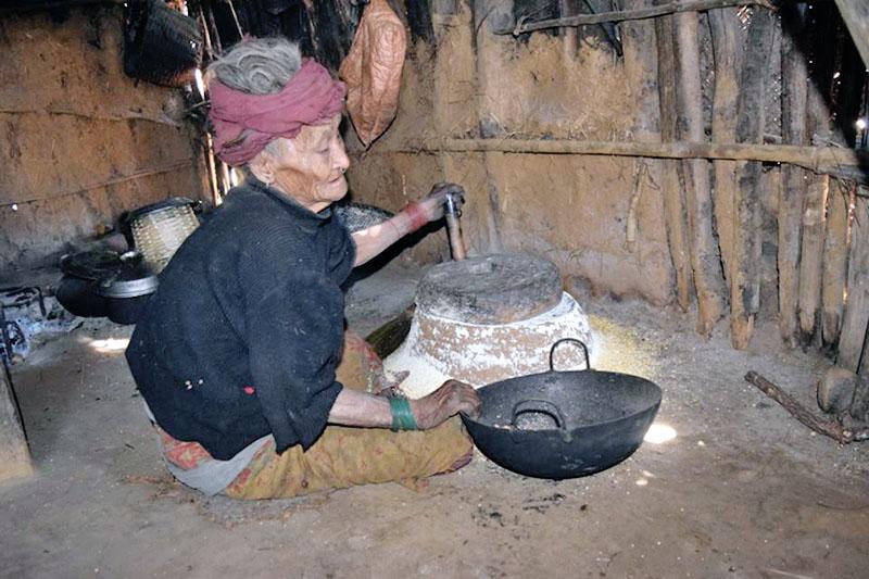 An elderly chepang woman grinding maize at a traditional stone grinder at Brussbang village in Dhading district, on Sunday, January 07, 2018. Photo: Keshav Adhikari